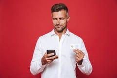 Beeld van de gelukkige mens in de witte creditcard van de overhemdsholding en smartp royalty-vrije stock afbeeldingen