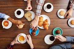 Beeld van de handen van mensen op houten lijst met croissants en koffie Stock Afbeelding
