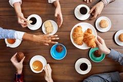 Beeld van de handen van mensen op houten lijst met croissants en koffie Royalty-vrije Stock Fotografie