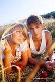 Beeld van de jonge mens en vrouw met appelen op tarwegebied Royalty-vrije Stock Afbeelding