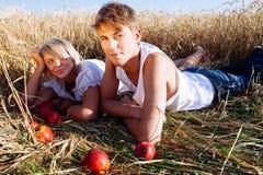 Beeld van de jonge mens en vrouw met appelen op tarwegebied Stock Foto's