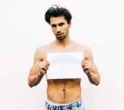 Beeld van de jonge mens met naakt torso die witte lege raad houden Royalty-vrije Stock Afbeeldingen