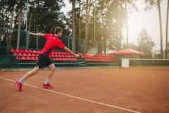 Beeld van de knappe jonge mens op tennisbaan Het speeltennis van de mens Mens die tennisbal werpen Mooi bosgebied zoals Royalty-vrije Stock Afbeeldingen