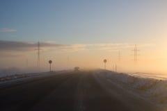 Beeld van de winterweg en auto in koud klimaat  stock fotografie