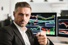 Beeld van de zakelijke mens die in bureau aan computer met grafiek en grafieken bij het scherm werken stock afbeelding