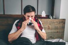 Beeld van een jonge mens met zakdoek De zieke kerel ligt in bed en heeft lopende neus de mens maakt een behandeling voor gemeensc stock foto's