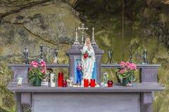 Beeld van een kleine kapel in een natuurlijke grot met het beeldje van Virgin van Lourdes royalty-vrije stock foto