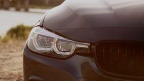 Beeld van een een koplamp en traliewerk van BMW bij zonsondergang royalty-vrije stock foto's