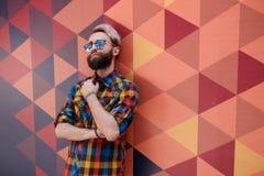 Beeld van een modieus jong model, gekleed in een veelkleurige T-shirt, die op zeshoeken stellen geometrische vormmuur stock afbeelding