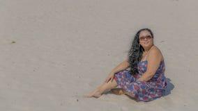 Beeld van een mooie gelukkige en het glimlachen vrouwenzitting op het zand in een blauwe kleding met rode en witte bloemen stock afbeelding