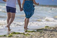 Beeld van een paar mensen die op de handen van de strandholding wandelen royalty-vrije stock foto's