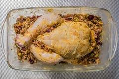 Beeld van een ruwe gehele kip met zijn rundergehakt die een glaskom klaar om worden gebakken invullen stock afbeeldingen