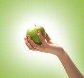Beeld van een smakelijke appel die in een menselijke hand wordt gehouden Stock Fotografie