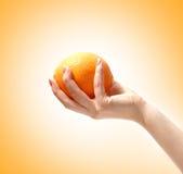 Beeld van een smakelijke sinaasappel in een menselijke hand Stock Foto