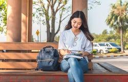 Beeld van een verbazende mooie vrouwenzitting op een bank in het boek van de parklezing royalty-vrije stock afbeeldingen