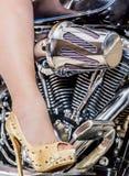 Beeld van een vrouwelijk been met gouden hielen met spijkers op een motorfiets royalty-vrije stock afbeelding