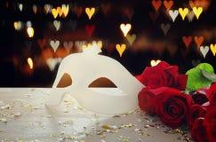 Beeld van elegant Venetiaans masker en rode rozen over houten lijst stock afbeeldingen