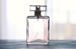 Beeld van elegante parfumfles achter lichte foto stock afbeeldingen