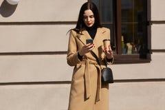 Beeld van ernstige jonge vrouw die elegante beige laag dragen gebruikend haar telefoon in zonnige stadsstraat en drinkend meeneem royalty-vrije stock afbeeldingen