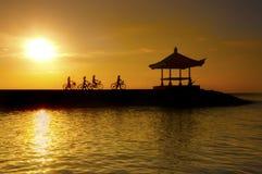 Beeld van fietsers die op een concrete barrière in het strand van Bali berijden Indonesië Sanur stock foto's