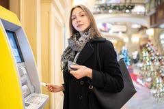 Beeld van gelukkig brunette met betaalpas bij ATM op vage achtergrond royalty-vrije stock afbeelding