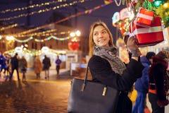 Beeld van gelukkig brunette met glas in handen dichtbij dozen met giften stock afbeelding