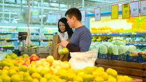 Beeld van gelukkig paar die goederen in supermarkt kiezen stock footage