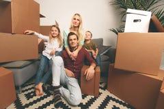 Beeld van gelukkig paar met kinderen die op vloer onder kartondozen zitten royalty-vrije stock foto's