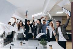 Beeld van gelukkige het commerciële team vieren overwinning in bureau Het succesvolle commerciële team werpt stukken van document stock afbeeldingen