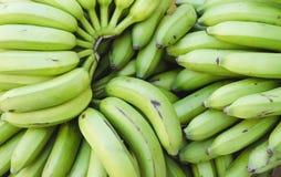 Beeld van groene bananen die voor verkoop worden gestapeld stock foto