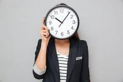Beeld van het Aziatische bedrijfsvrouw verbergen achter een klok royalty-vrije stock foto's
