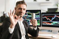 Beeld van het blije pak van de zakenmanholding van geld terwijl het werken in bureau met grafiek en grafieken aan computer stock afbeeldingen