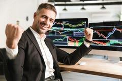 Beeld van het blije zakenman werken in bureau aan computer met grafiek en grafieken stock foto