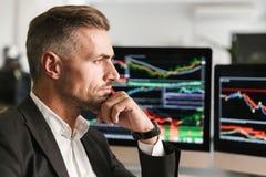 Beeld van het ernstige zakenman werken in bureau aan computer met grafiek en grafieken bij het scherm stock foto's