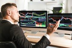 Beeld van het ernstige zakenman werken in bureau en het kijken op computer met grafiek en grafieken royalty-vrije stock foto