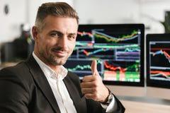 Beeld van het Europese zakenman werken in bureau aan computer met grafiek en grafieken bij het scherm stock afbeeldingen