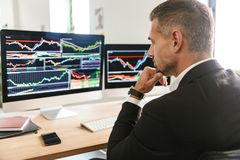 Beeld van het geconcentreerde zakenman werken in bureau en het kijken op computer met grafiek en grafieken bij het scherm royalty-vrije stock foto's