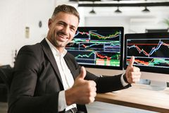 Beeld van het gelukkige zakenman werken in bureau aan computer met grafiek en grafieken bij het scherm royalty-vrije stock afbeelding