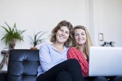 Beeld van het glimlachen twee jonge vrouwenzitting op de bank met laptop royalty-vrije stock foto