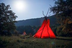 Beeld van het kamperen met rode tipi en mensen dichtbij vuur op donkere bosachtergrond Verbazende landschapsachtergrond stock fotografie