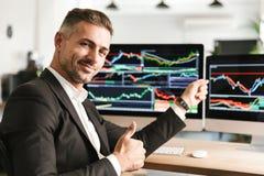 Beeld van het Kaukasische zakenman werken in bureau aan computer met grafiek en grafieken bij het scherm stock afbeelding