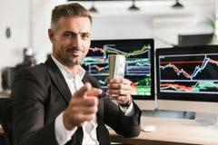 Beeld van het knappe pak van de zakenmanholding van geld terwijl het werken in bureau met grafiek en grafieken aan computer royalty-vrije stock fotografie