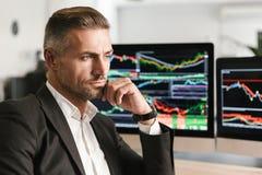 Beeld van het knappe zakenman werken in bureau aan computer met grafiek en grafieken bij het scherm royalty-vrije stock foto's