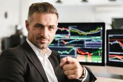 Beeld van het mooie zakenman werken in bureau aan computer met grafiek en grafieken bij het scherm stock foto
