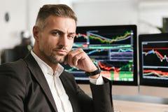 Beeld van het succesvolle zakenman werken in bureau aan computer met grafiek en grafieken bij het scherm stock fotografie