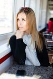 Beeld van het wachten van op mobiel telefoongesprek mooie vrolijke blonde jonge bedrijfsvrouw met groene en ogen die weg ontspann Stock Foto