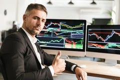 Beeld van het zekere zakenman werken in bureau aan computer met grafiek en grafieken royalty-vrije stock afbeeldingen