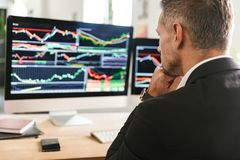 Beeld van het zekere zakenman werken in bureau en het kijken op computer met grafiek en grafieken stock afbeelding