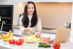 Beeld van jong Aziatisch meisje met mok en laptop die zich bij lijst met groenten en vruchten bevinden stock afbeeldingen