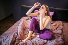 Beeld van jonge en mooie vrouwenzitting in pyjama's op bed en van het gebruiksoog dalingen voor ogen Zij is geconcentreerd op dat royalty-vrije stock foto